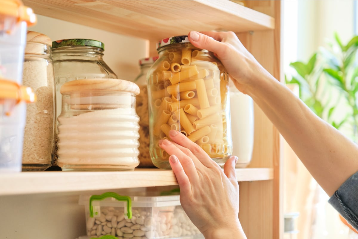 Woman reaching for pasta stored in a clear jar on clean and organized pantry shelves