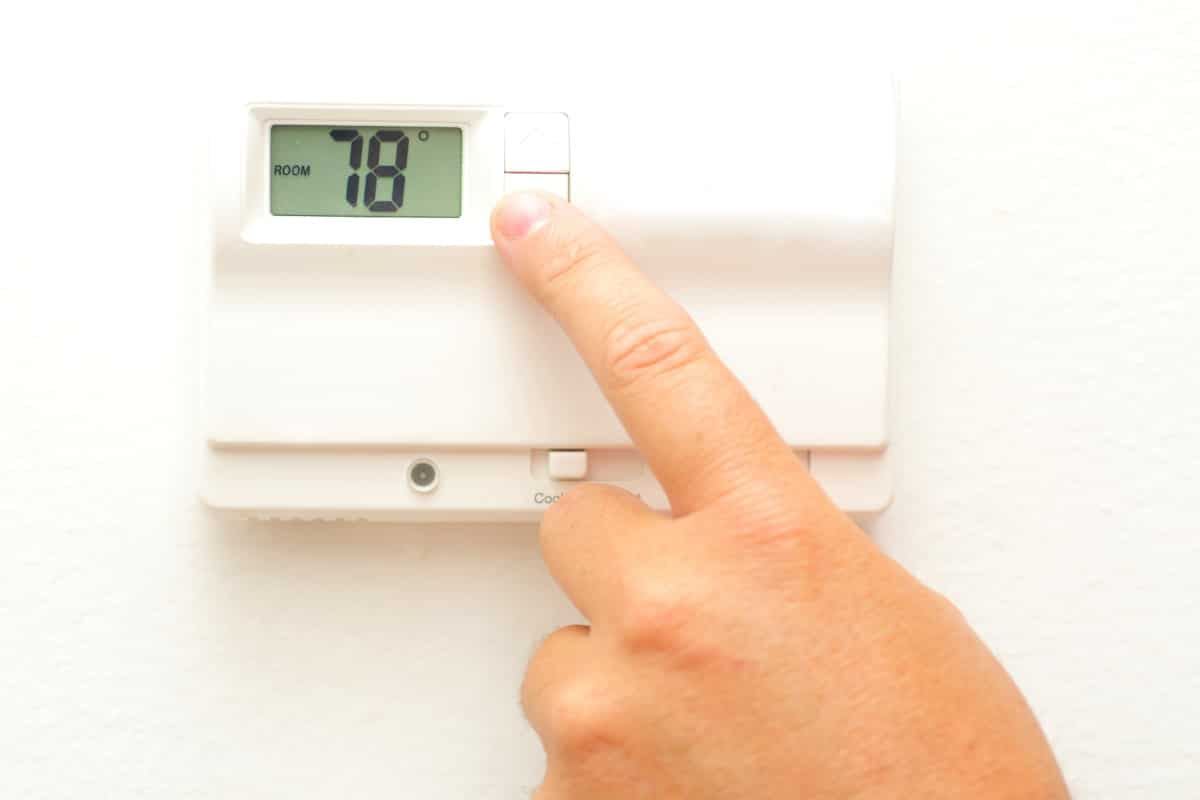 Hand adjusting thermostat on wall