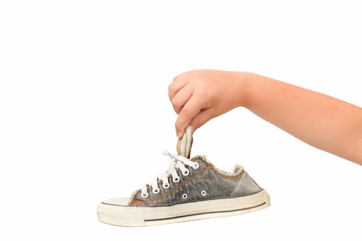 Hand holds a smelly canvas lace-up sneaker