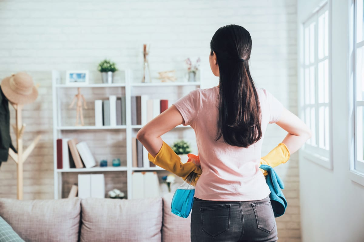 Back view of woman with hands on hips holding cleaning supplies and looking at cluttered shelves