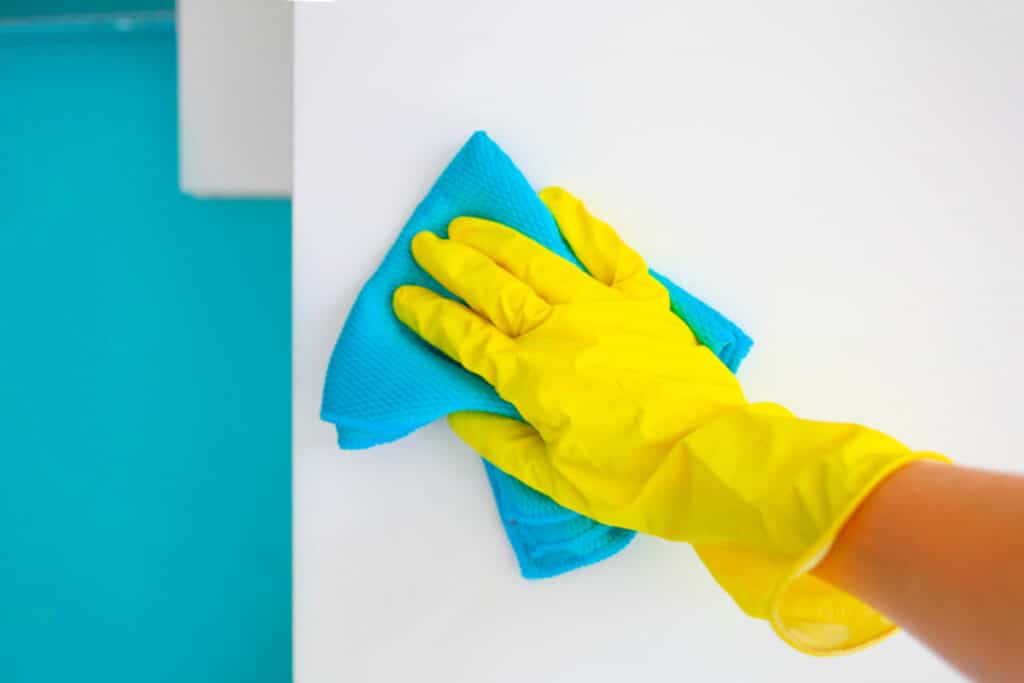 Hand in rubber glove uses microfiber cloth to get hairspray off bathroom wall