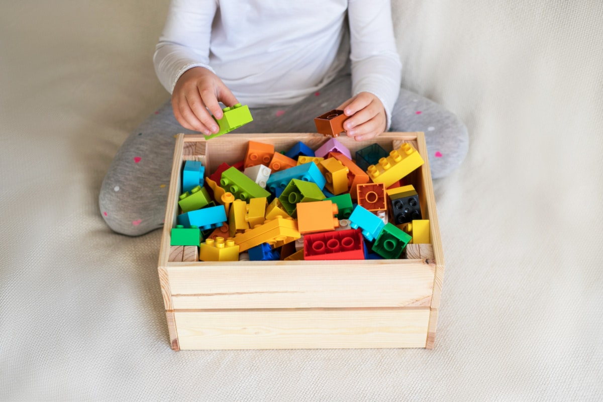 Child playing cleaning game to put away Legos in wooden crate on bed