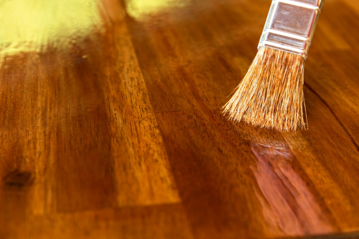 Closeup of paint brush applying finish to repair scratch on wood table