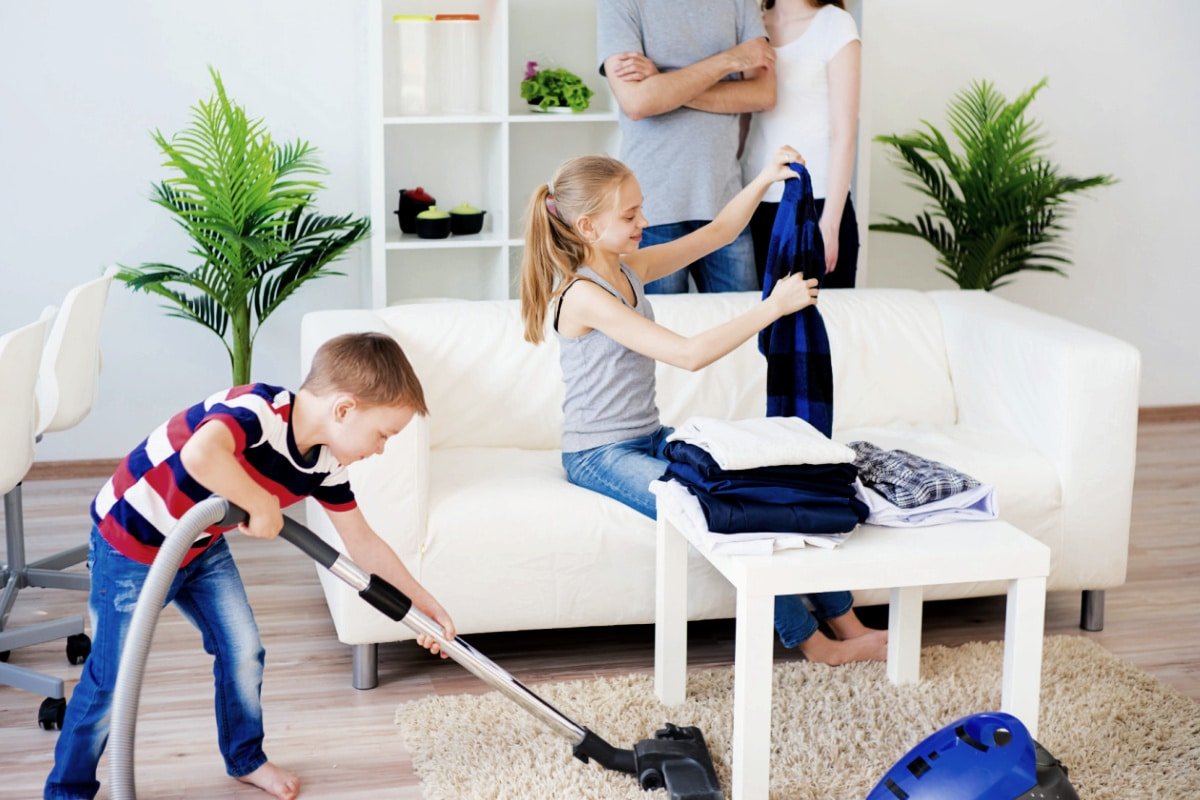 Parents watch as boy helps clean house by vacuuming and girl folds laundry on sofa.