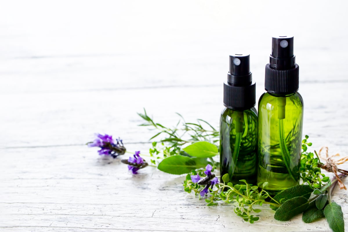 Two pump spray bottles containing homemade air freshener spray sitting on top of fresh herbs