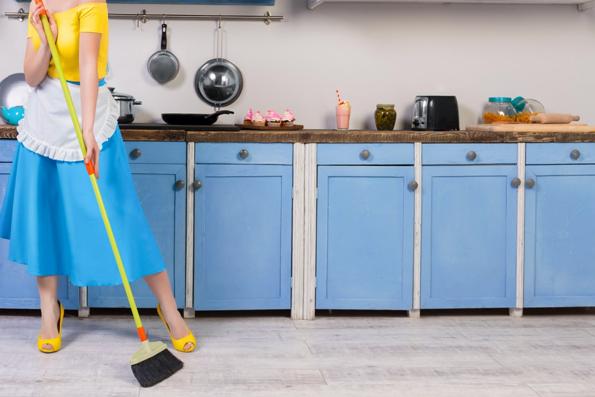 Woman dressed in old-fashioned skirt and blouse with ruffled apron and high heels and using a broom to sweep a kitchen.