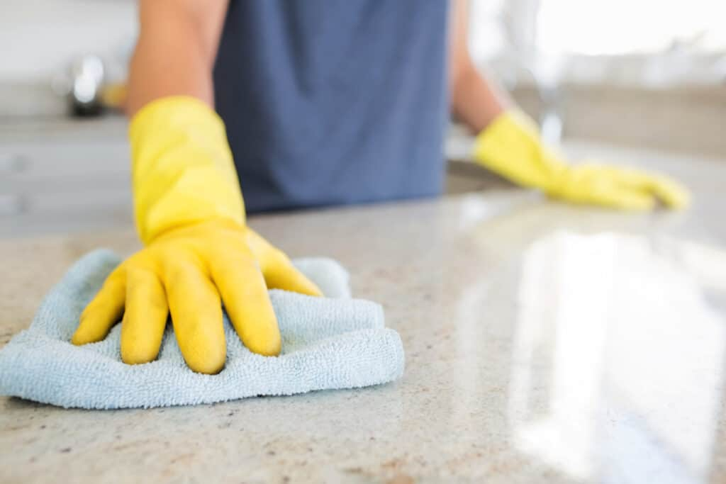 Woman polishing countertop with homemade granite cleaner