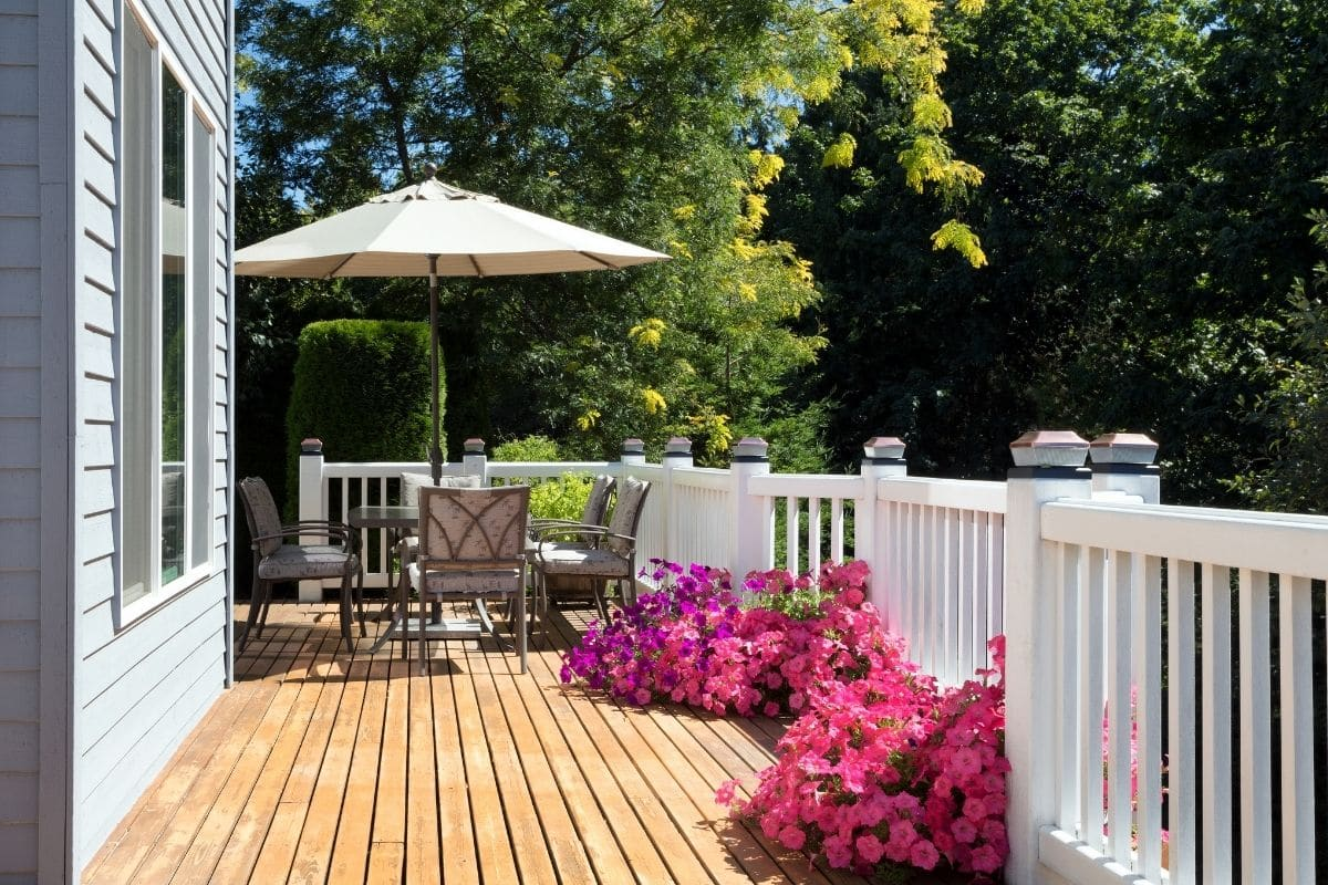 Patio table with an umbrella sits on a clean wood deck attached to a suburban home.