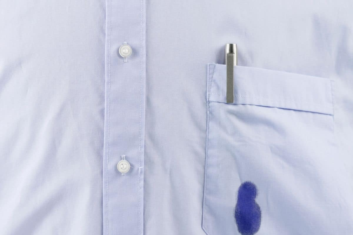 Man's button up shirt with a broken ballpoint pen making an ink stain on the front pocket