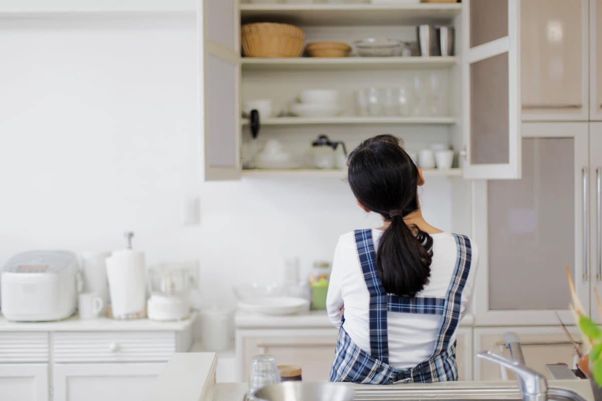 Rear view of woman leaning against sink as she tries to decide how to organize open kitchen cabinet