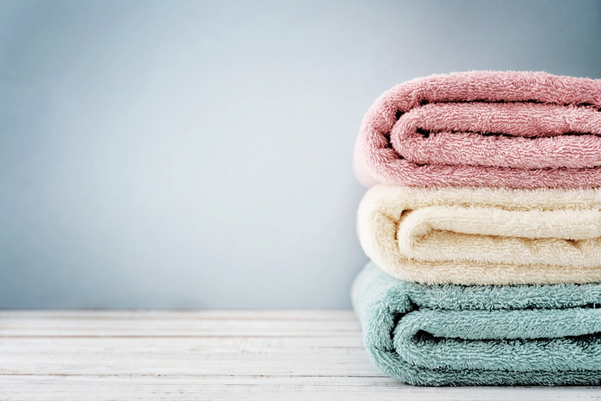 Three neatly folded towels on a wood counter