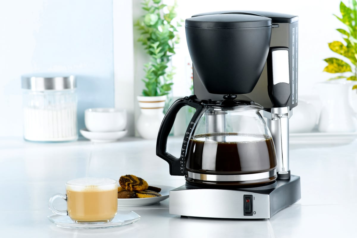 Clean coffee maker on a white kitchen counter with a freshly-brewed cup and plate of cookies