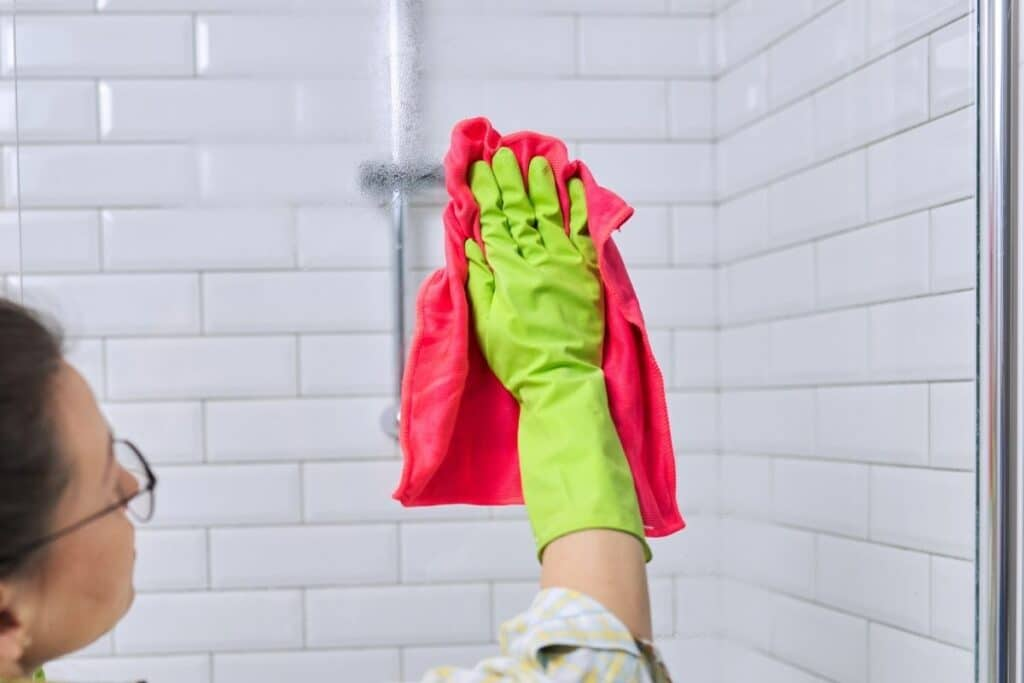 Woman removing soap scum from glass shower doors