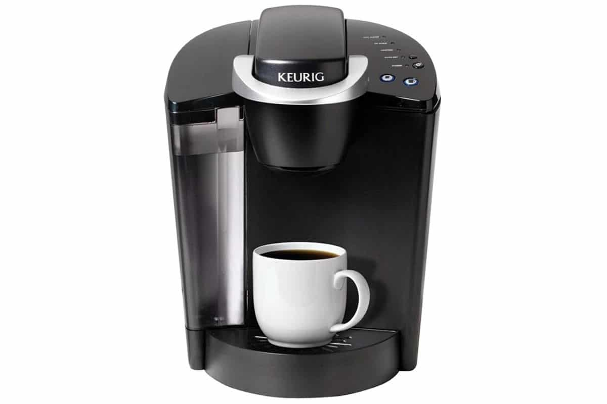 Clean black Keurig coffee maker with a full white cup that just brewed.