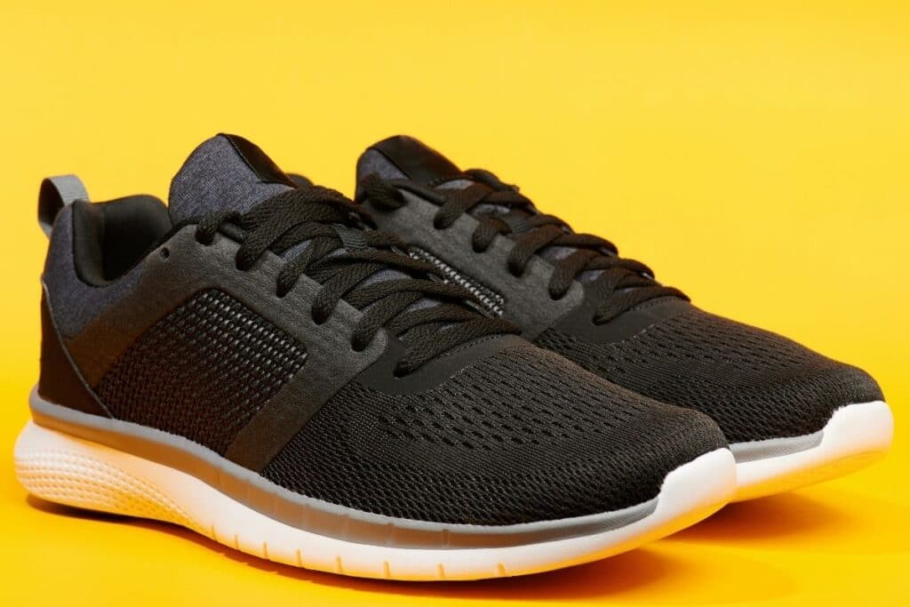 Closeup of a pair of black running shoes on a yellow background