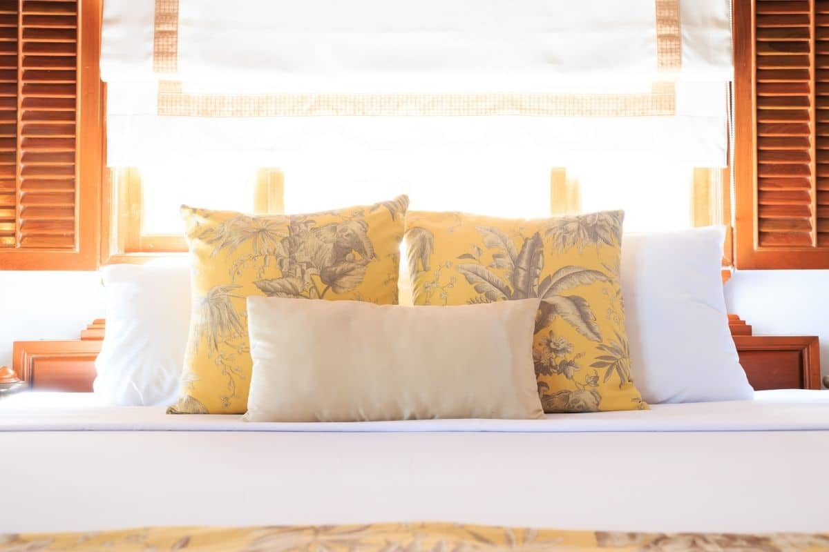 Assorted sizes of pillows arranged on a bed positioned beneath a sunny window