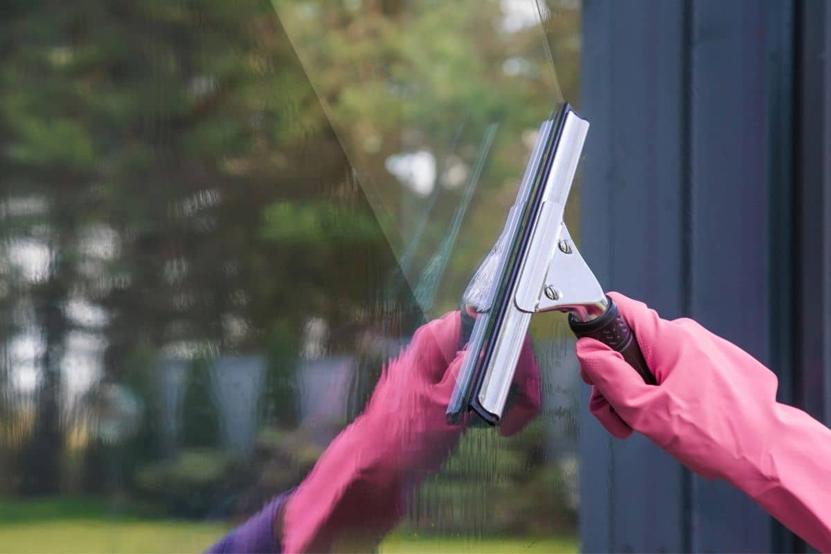 Hand in rubber glove uses a squeegee to wash windows without leaving streaks