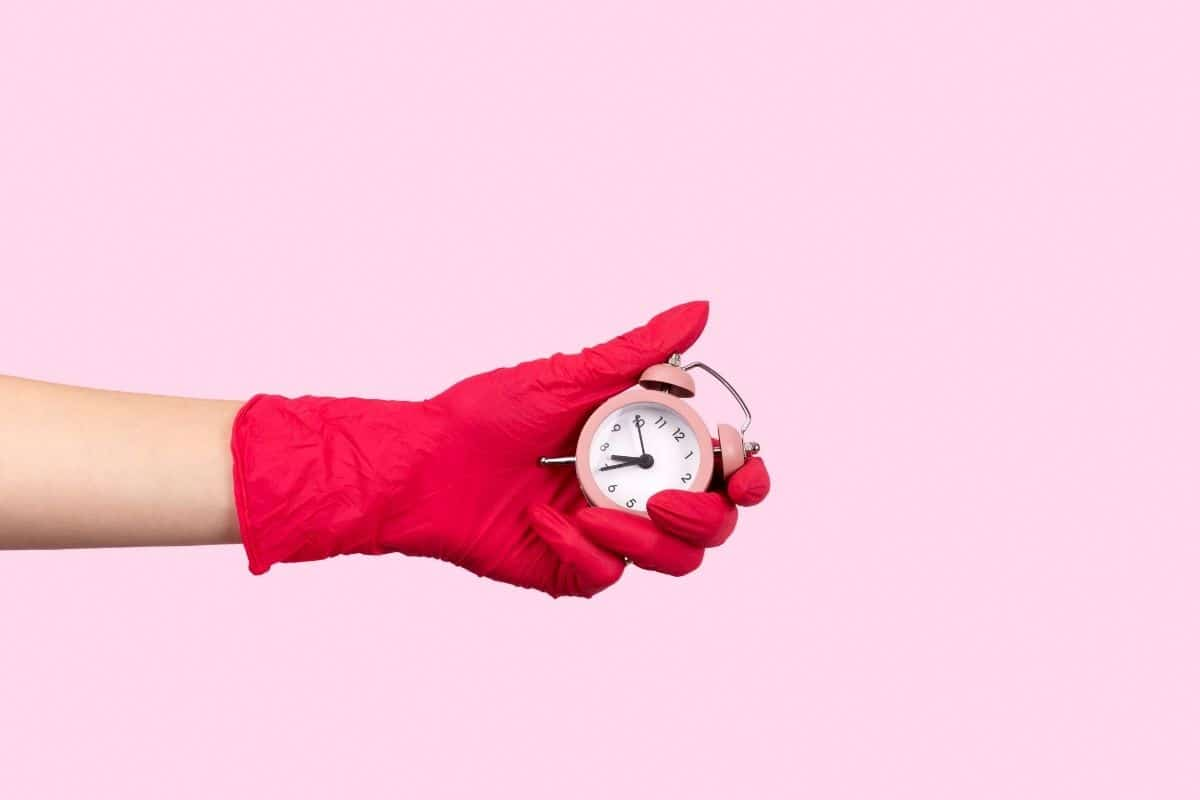 Hand in rubber cleaning glove holds a tiny old-fashioned alarm clock with a one-minute timer