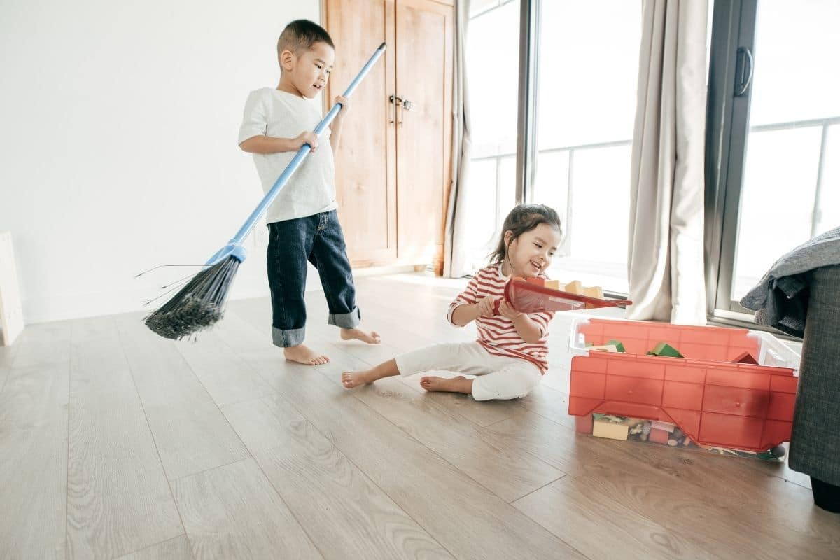 Two small children sweeping floor and picking up toys which are age-appropriate chores from the list