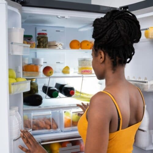 Young woman stares into open refrigerator which reduces its efficiency