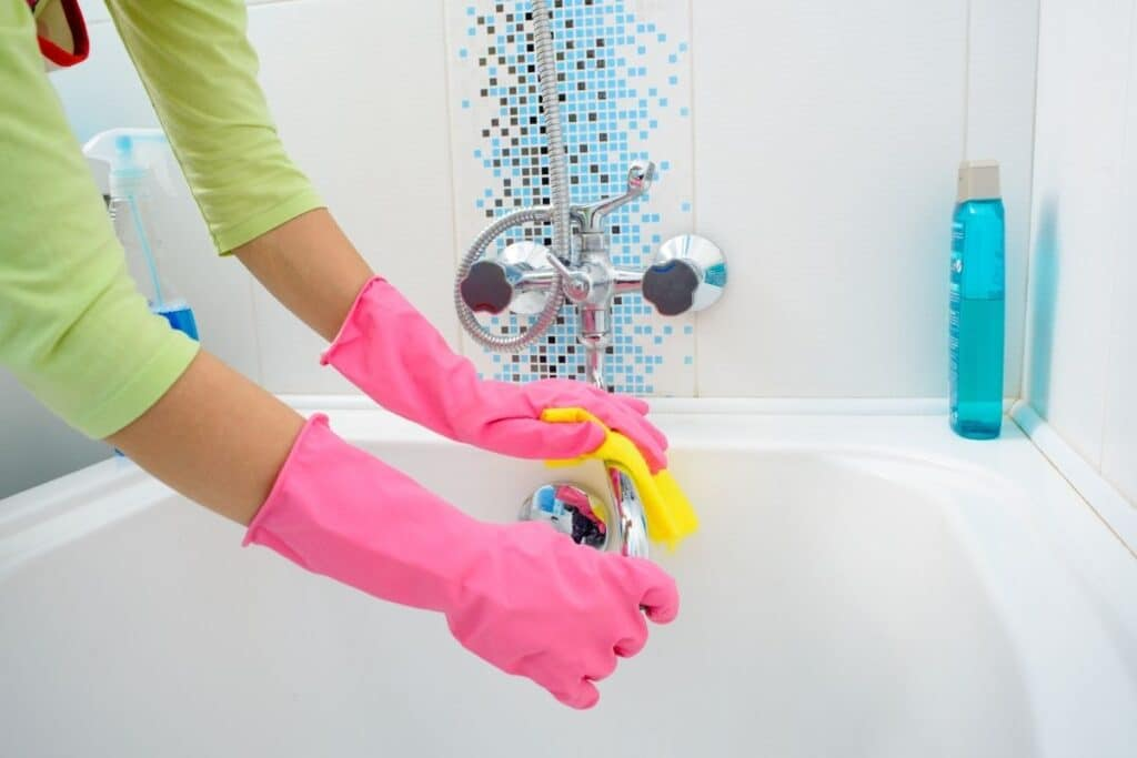 woman wiping homemade bathroom disinfectant spray off of tub faucet
