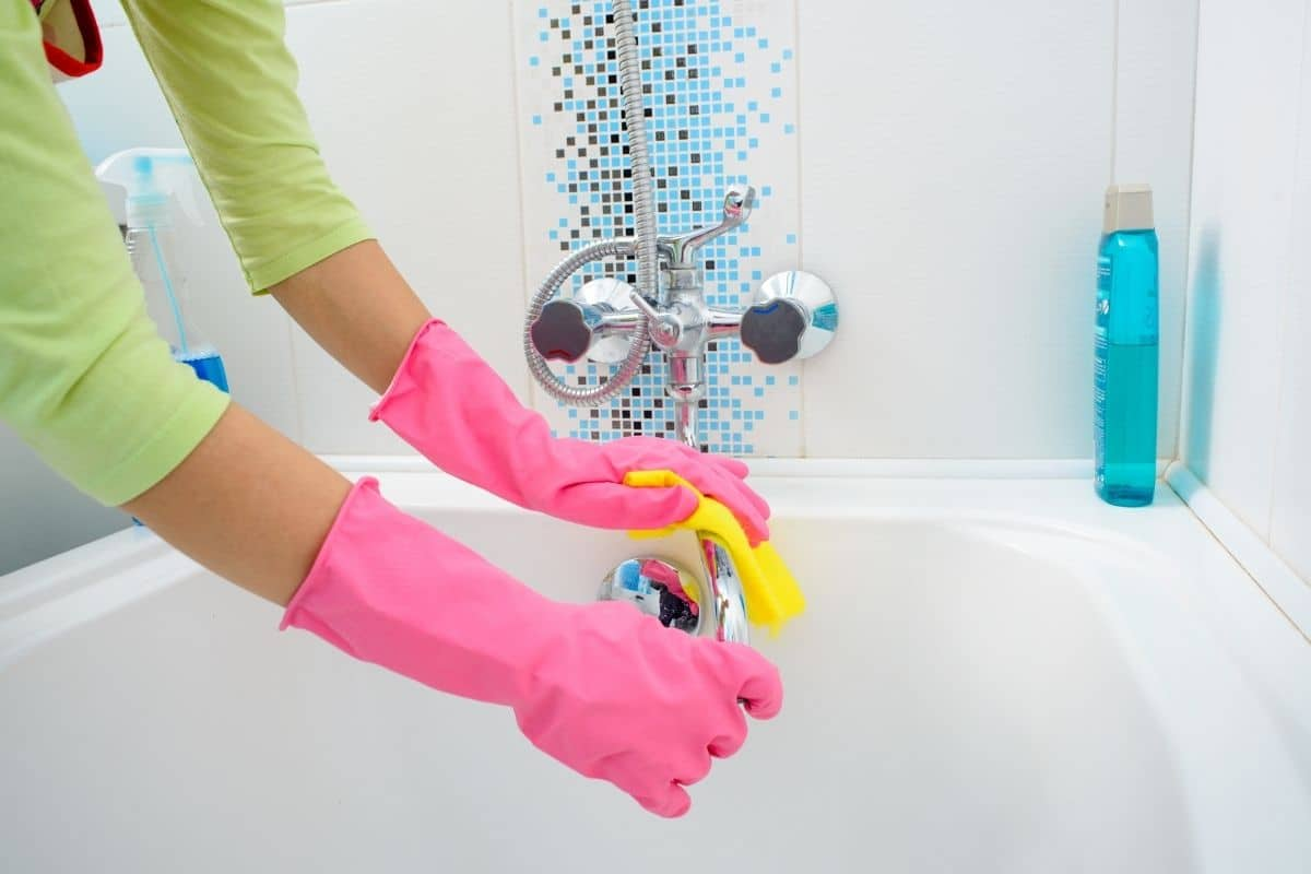 Woman wearing cleaning gloves uses a microfiber cloth to wipe homemade bathroom disinfectant spray off of bathtub faucet