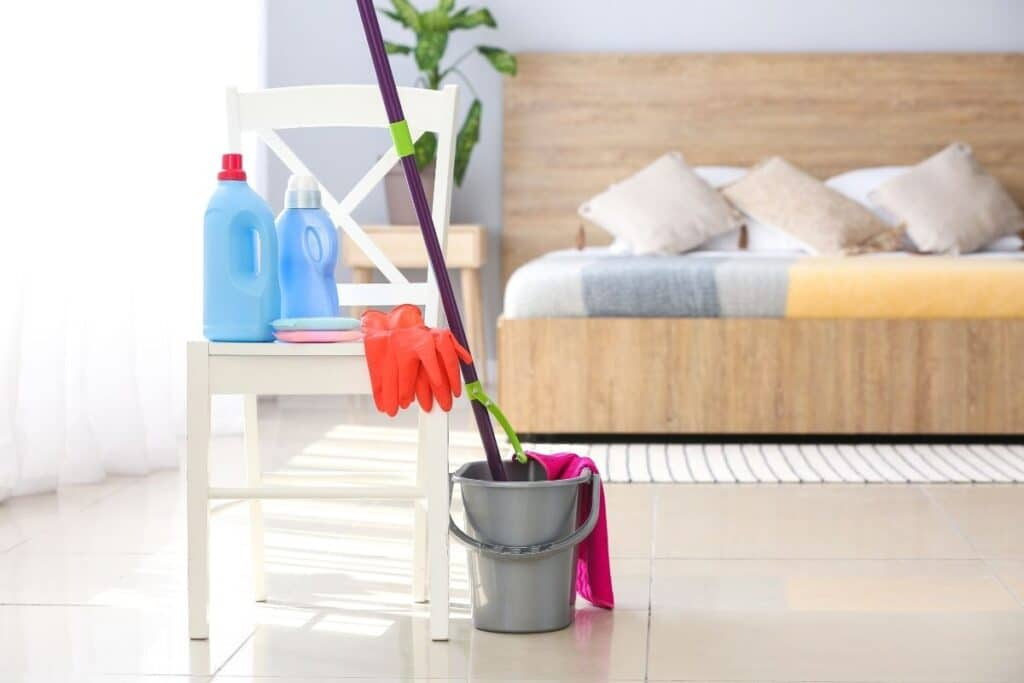 Mop in a bucket and other tools to clean bedrooms sitting on a chair
