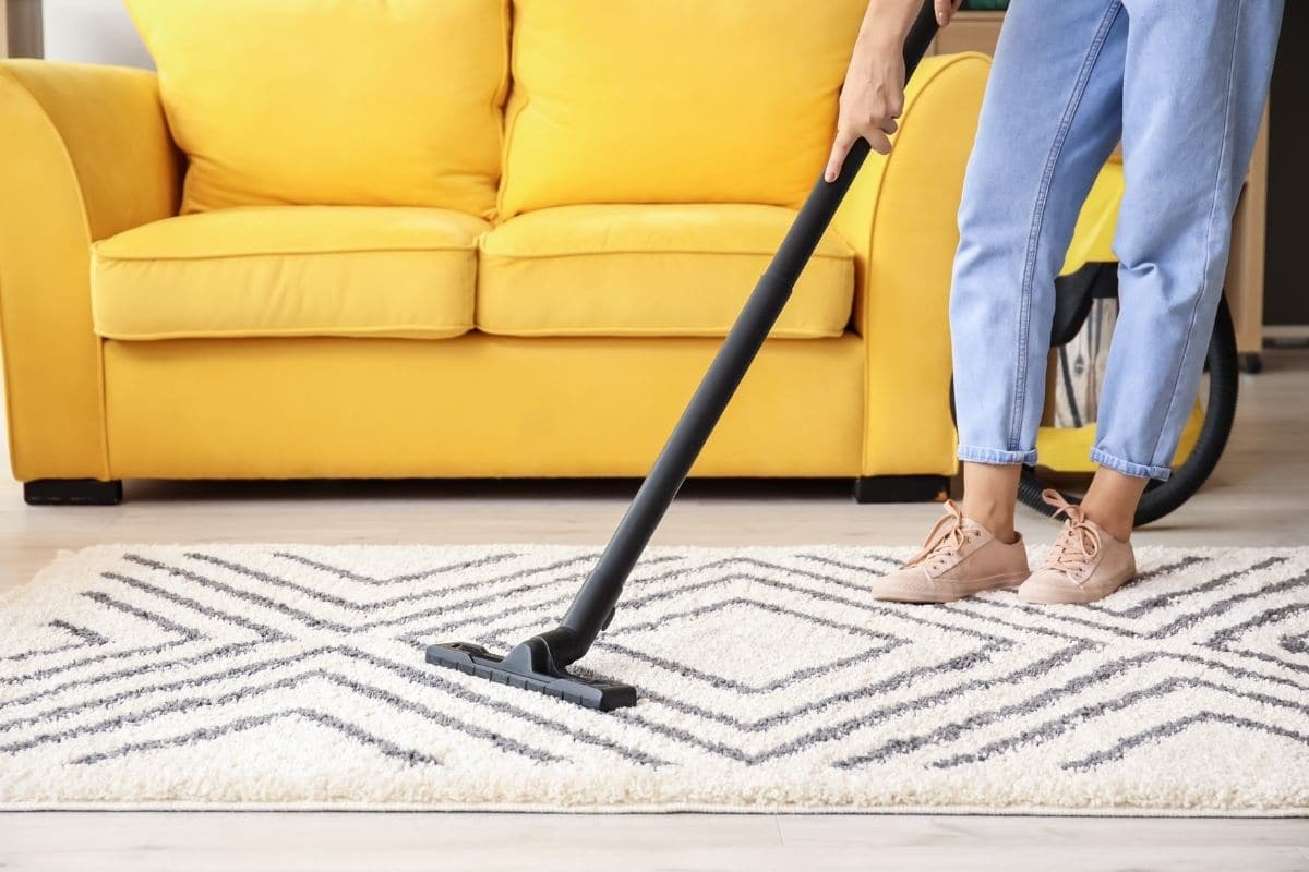 Person performing daily house cleaning routine by vacuuming area rug in front of sofa in living room