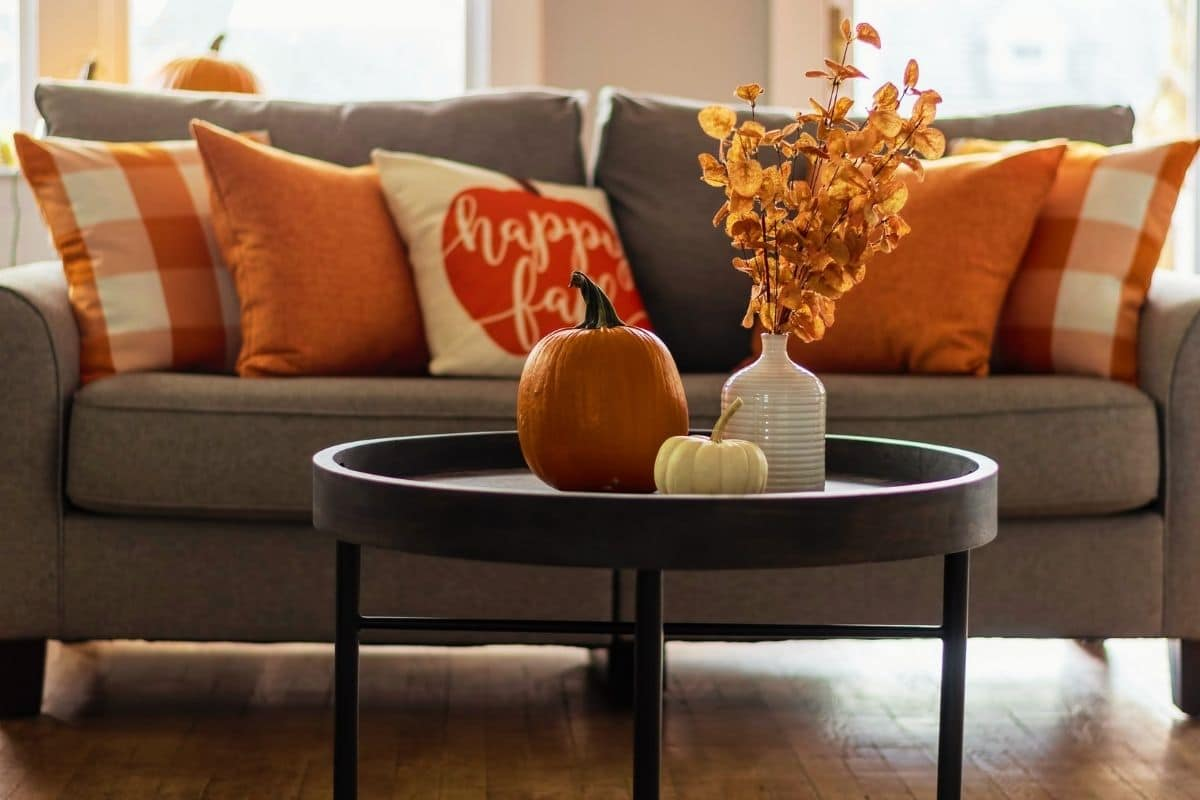 Cozy autumn pillows and pumpkin decor in a home after following a Fall Cleaning Schedule