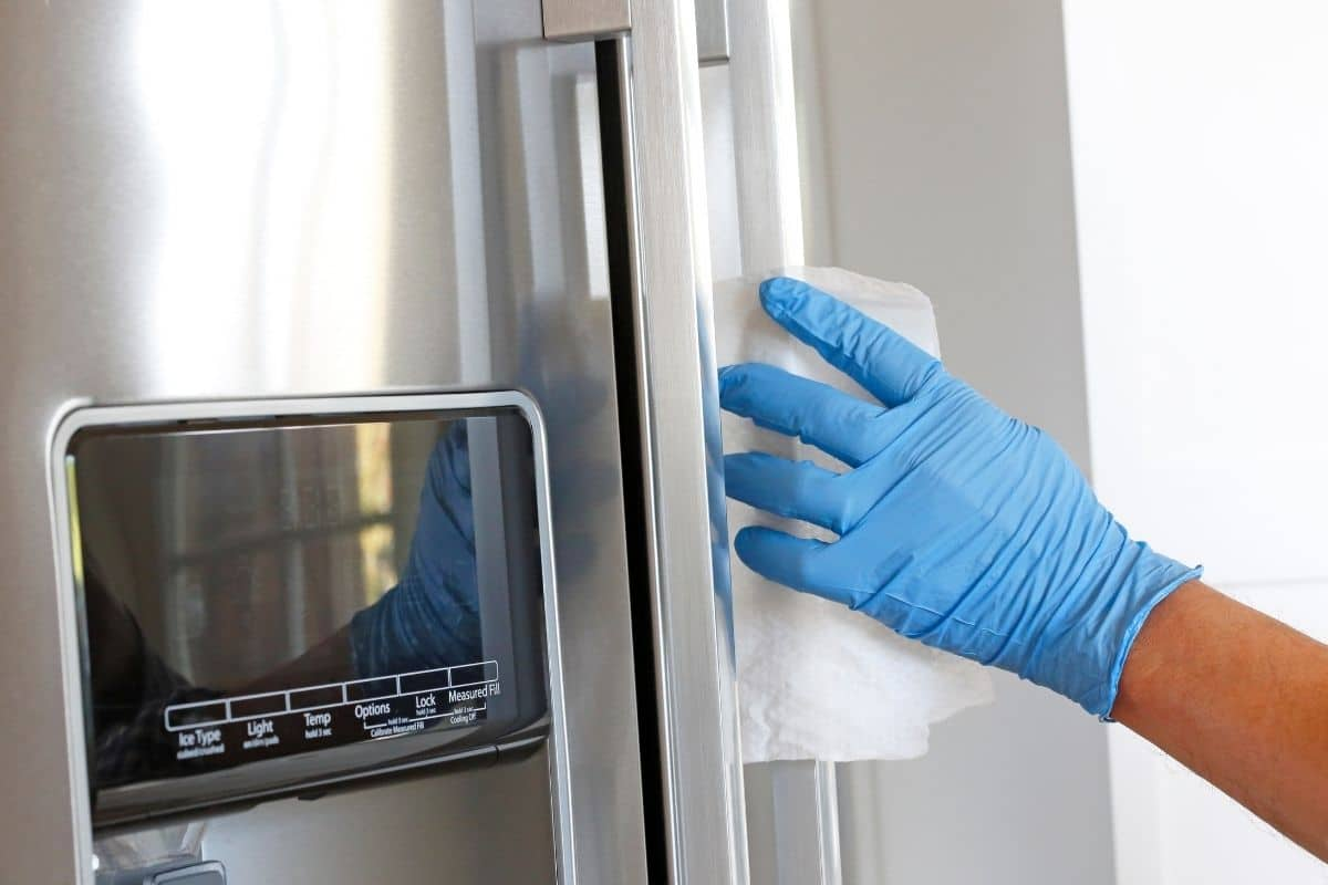 Person wearing a latex glove uses a homemade disinfecting wipe to clean a stainless steel refrigerator handle