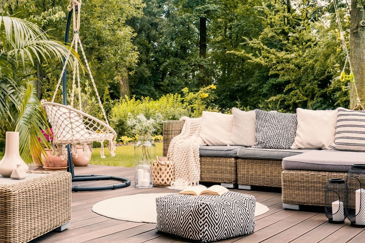 Wood deck featuring freshly cleaned patio furniture with boho black and white cushions and a hanging chair